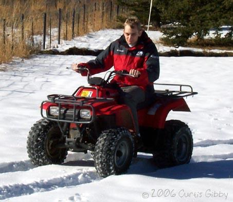 Curtis riding a 4-wheeler in the snow