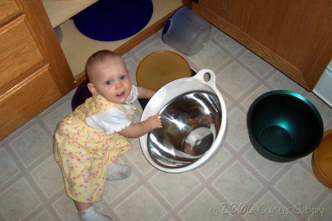 Audrey plays in the bowl cupboard