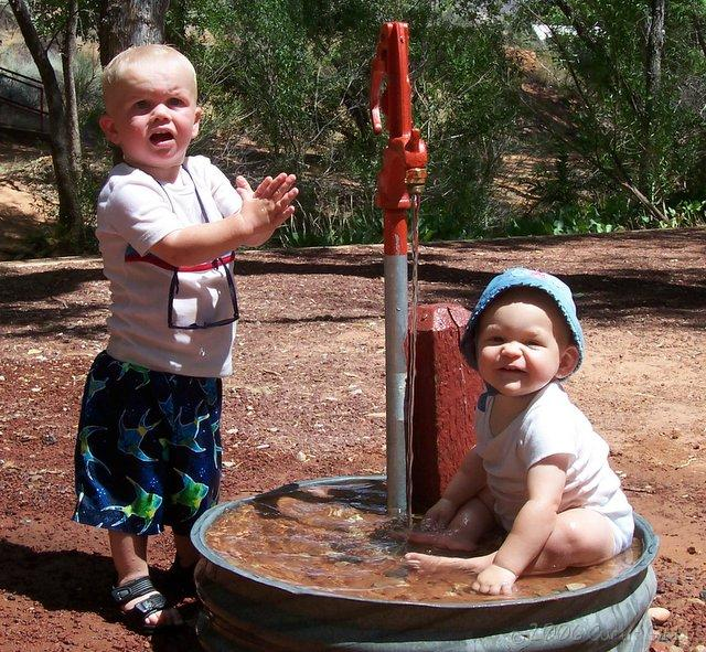 Audrey and Andrew play in a spigot after our hike at Red Cliffs Campground