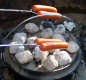 View - The hot dogs cook over the coals on the dutch oven